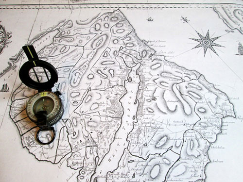 photograph of an old map with a compass.